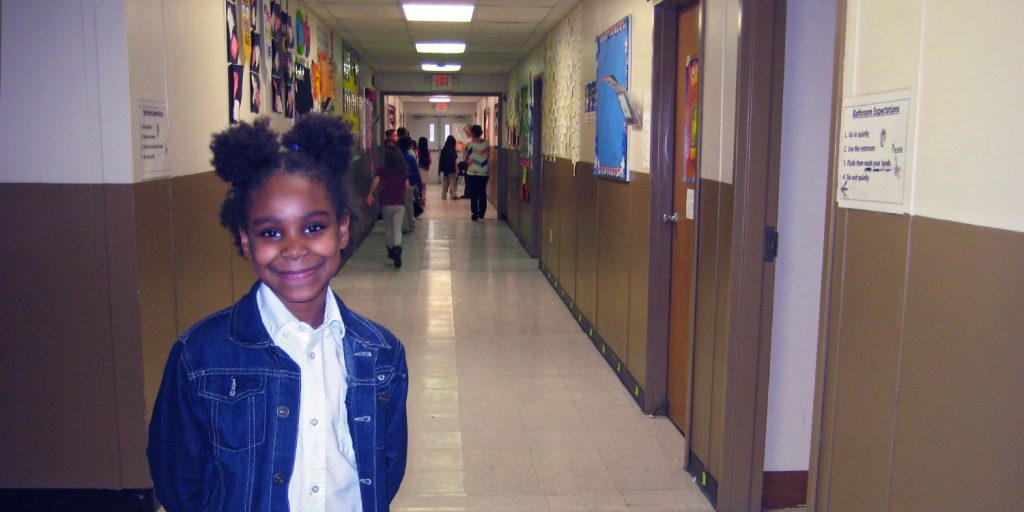 Elementary student smiling in hallway.
