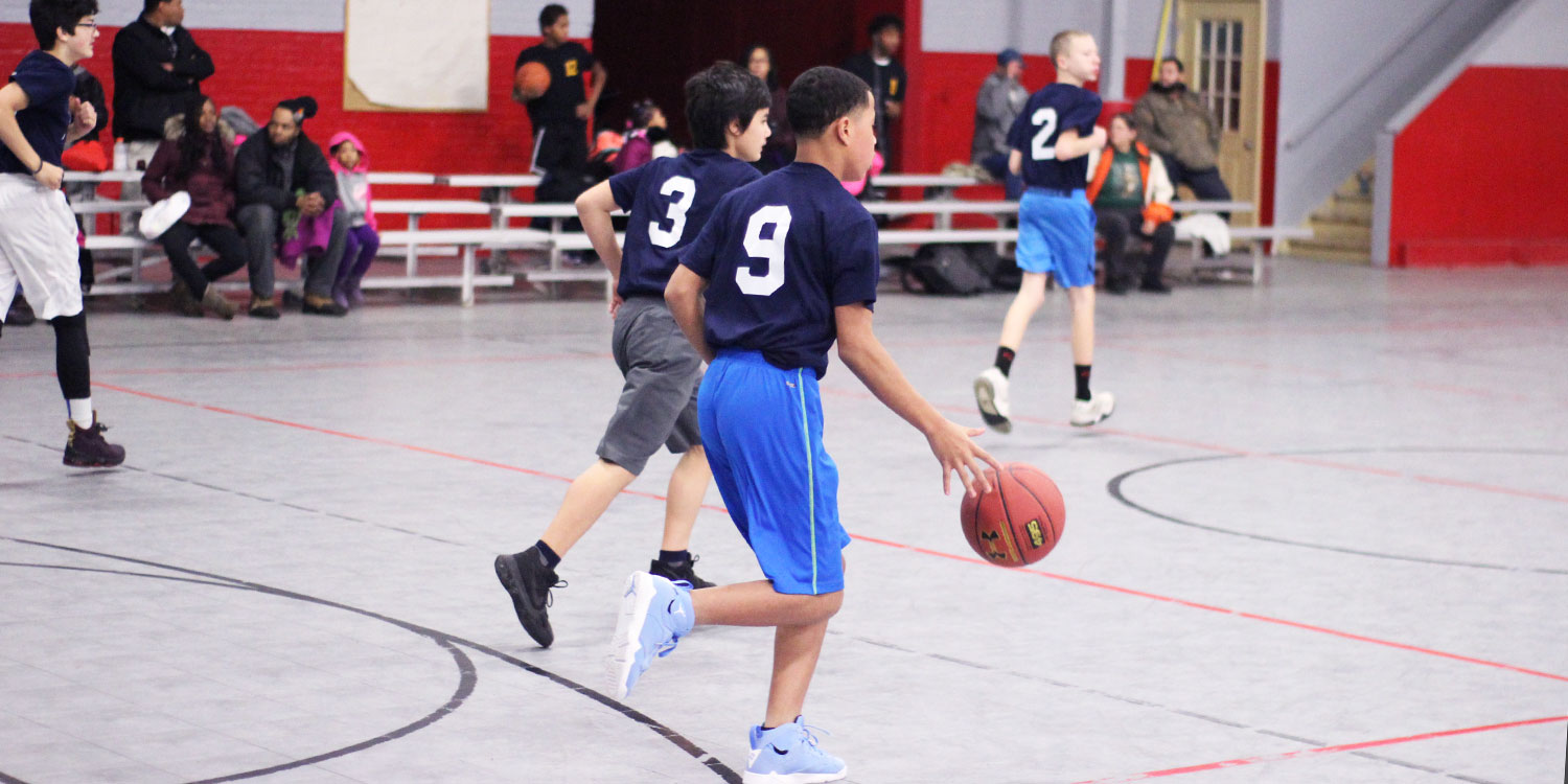 Students playing in a basketball game.